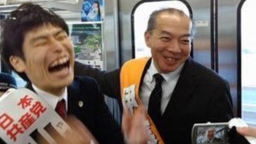 電車内で候補者名入りタスキをかけて爆笑する山添拓と伊藤岳