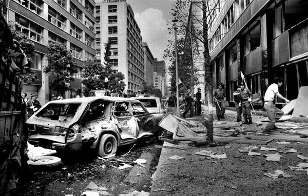 三菱重工ビル(右)で起きた爆弾テロでは乗用車はつぶれ、路上一面にガラスが散乱した=昭和49年8月30日、東京都千代田区丸の内